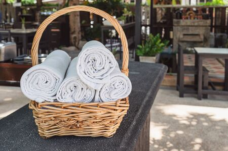 Folded roll towels stacked in wooden basket on the counter