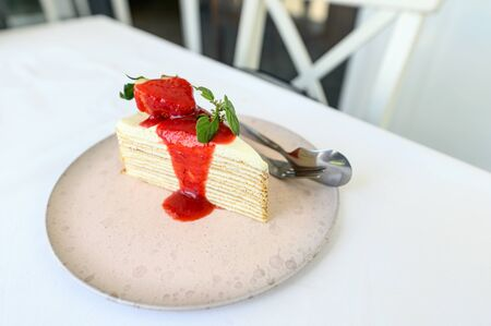 Strawberry crepe cake with strawberry sauce on ceramic plate