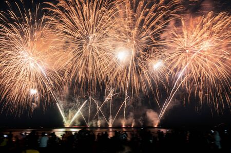 Spectators are watching colorful fireworks in the night sky on the beach at annual festive