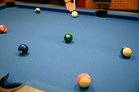 Player aiming green ball billiard on blue billiard pool table