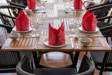 Set of wooden dining table with crockery, wine glass and red napkin in restaurant