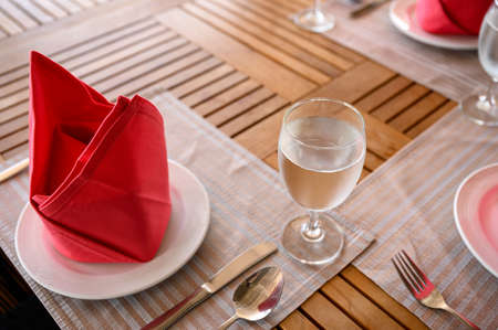 Served dining wooden table set with ceramic tableware, silver utensil, red napkin and water Stock fotó