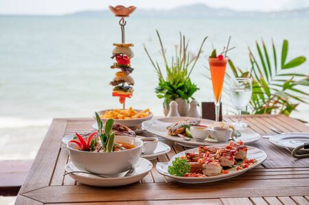 Variety of food, roasted pork ribs, beef steak, seafood and spicy soup on dining table in tropical sea