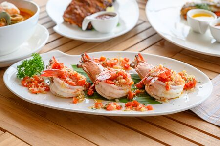 Spicy chili grilled prawns in white plate on dining table