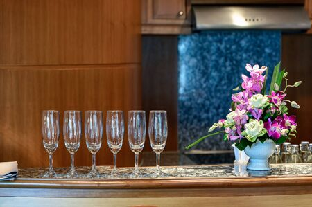 Row of wine glass with flower decoration on marble bar in kitchen Reklamní fotografie