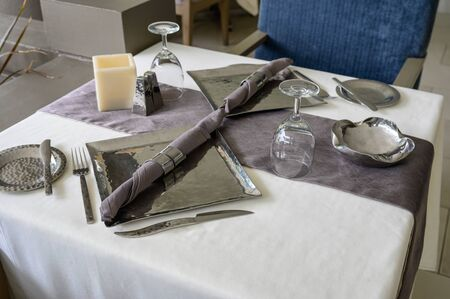 Dining stainless set with cutlery, plate, wine glass on tablecloth