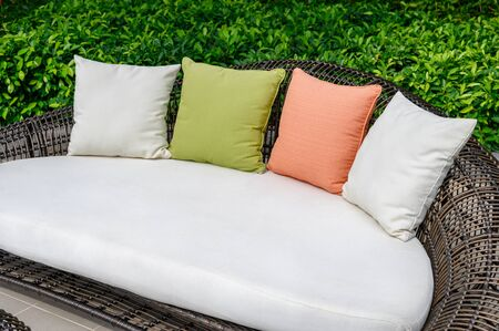Pillows on mattress and weave wooden sofa in the garden Reklamní fotografie - 134791390