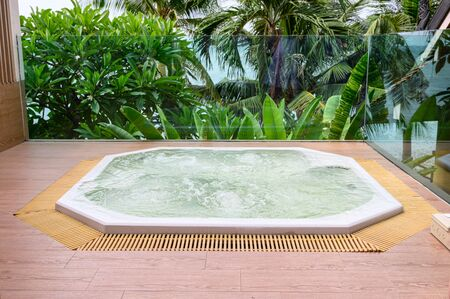 Luxury bathtub with water streaming installation on wooden patio with garden on sea