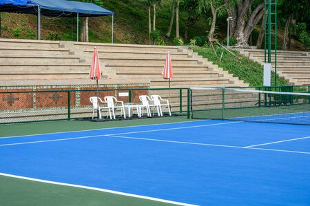 Synthetic rubber field in tennis court with chairs and parasols