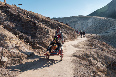 East Java, Indonesia - Sep 11 2018 : Tourists sitting on trolley service from villager on volcano at Kawah Ijen