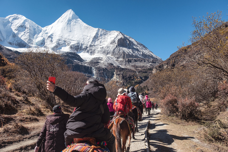 Daocheng, China - Oct 23 2018 : Group of tourists riding horse into holy valley with Yangmaiyong mountain at Yading national park Reklamní fotografie - 134758751