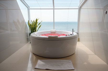 Pattaya, Thailand - May 26 2019 : Luxury jacuzzi bathtub with colorful flower in water with sea and sky view Redakční