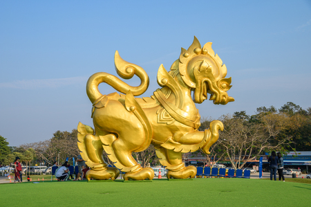 Chiang Rai, Thailand - Feb 13 2019 : Golden big statue singha icon on green hill at singha park