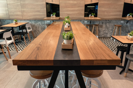 Bangkok, Thailand - Dec 14 2018 : Wooden large table with chairs and plant decoration in cafe