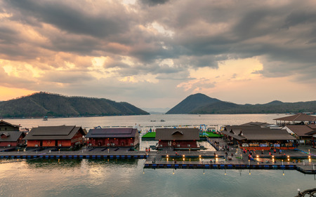 Kanchanaburi, Thailand - Apr 06 2019 : Tourists relaxing on wooden raft resort floating on Srinakarin dam in evening at Ananta river hills, Kanchanaburi