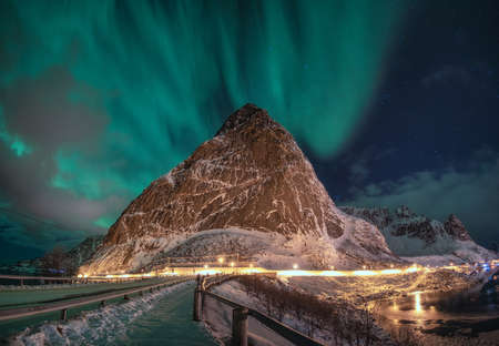 Panorama of Aurora Borealis with star over snowy mountain in Reine at Lofoten Islands, Norway