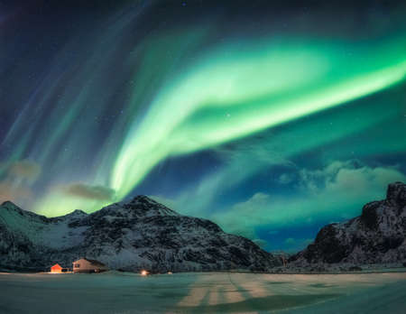Aurora Borealis or Northern Lights over snowy mountain on Arctic Circle in Flakstad at Lofoten islands, Norway