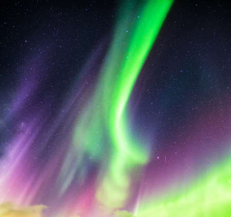 Aurora Borealis or Northern lights green and purple colors with starry in night sky on Arctic circle 免版税图像