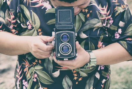 Man rotating vintage film camera with looking on above 写真素材 - 156439726