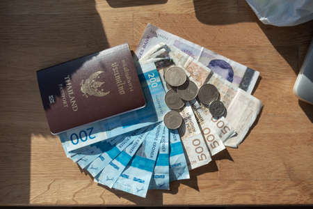 Currency Norway Kroner banknote with Coins and Thailand Passport on wooden table Reklamní fotografie