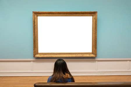 Spectator looking blank large golden frame on blue wall in art gallery