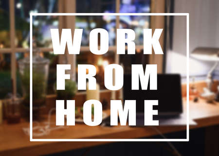 Work from home message concept. Laptop with flora decoration with lighting on wooden counter in house at night Reklamní fotografie