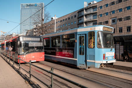 Oslo, Norway - Mar 27 2018 : Red and blue Tram with passenger running on electric rail with buildings in downtown Redakční