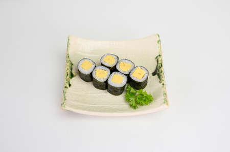 Tamago maki sushi roll seaweed with japanese rice on ceramic plate