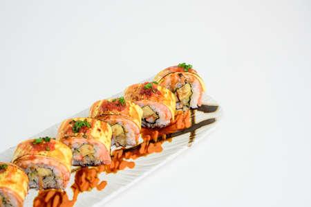 Deep fried shrimp tempura sushi nigiri with breadcrumbs and seaweed on white plate