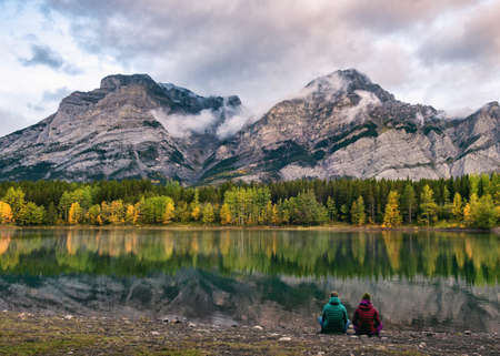 Couple traveler relaxing on coastline in Wedge pond at Kananaskis country, Canada Imagens