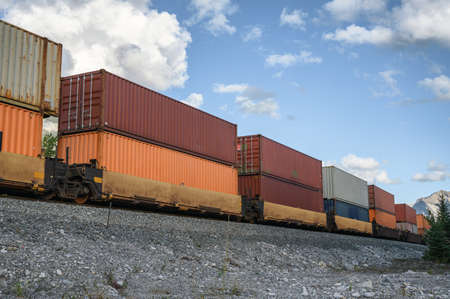 Train long freight passing with container loading on railway in valley at Calgary, Canada Imagens