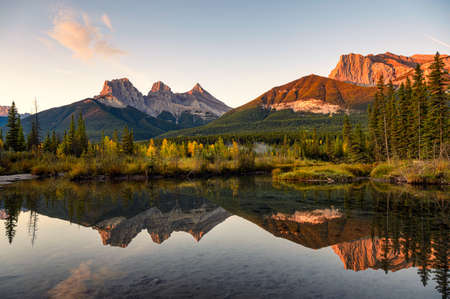 Scenery of Three sisters mountains reflection on pond at sunrise in autumn at Banff national park, Canada
