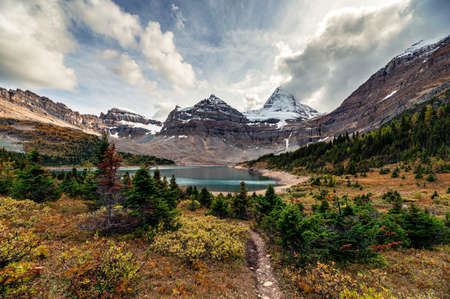 Mount Assiniboine with autumn forest at Lake Magog on provincial park, Canada Imagens