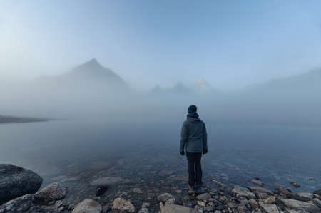 Man traveler standing on Lake Magog with Mount Assiniboine in foggy at provincial park, Canada Imagens