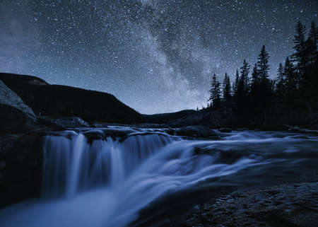 Waterfall rapids flowing on rocks in pine forest on evening at Elbow falls, Kananaskis