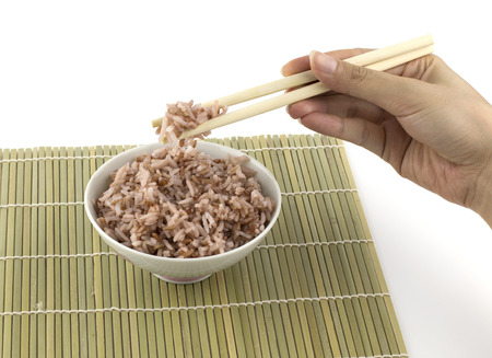 clamped: Cooked red rice got clamped by chopstick