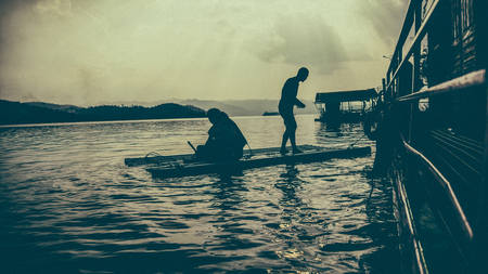 Silhouette people on boat at river vintage and summer holidays concept Stock Photo