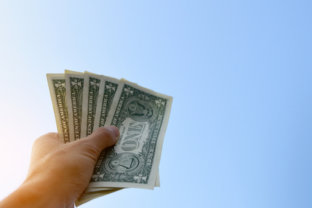 Hand holding dollar money against blue sky on background,Business Investment and saving concept