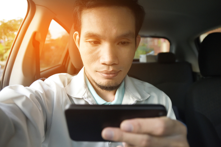 Man using smartphone to shopping and play games and reading e mail online by internet in a car Stock Photo