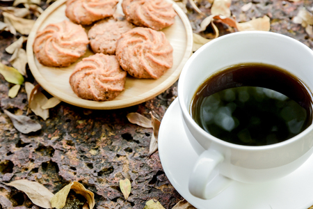 Coffee is served in a white cup, placed on a wooden table with a cookie. It is a snack at leisure. Stock Photo