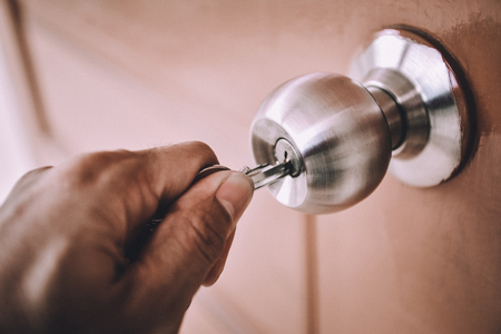 Hand is opening the door knob with the key. Stock Photo