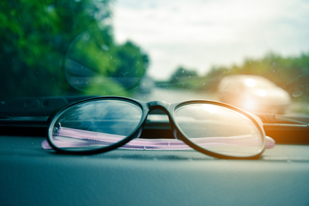 glasses and phone in car parked on road