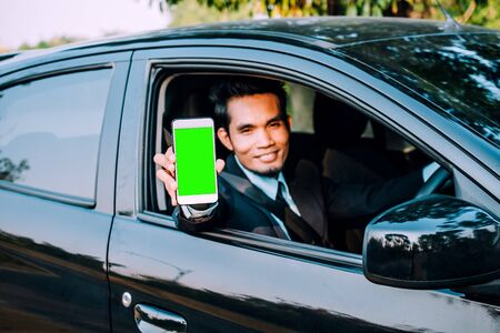 Man holding mobile smartphone showing on phone screen and sitting car Stockfoto