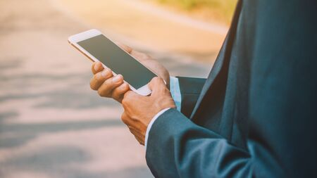 Businessman holding mobile smartphone Banco de Imagens