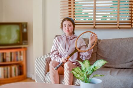 Asian women beauty cute holding tennis racket sitting in room happy smile