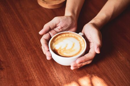Close up Hand holding coffee cup of People are in coffee shop Stock fotó