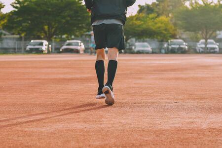 Runner Man jogging or running in evening at sunlight