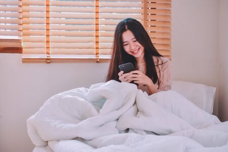 Women holding Mobile smartphone sitting on bed in room Stock fotó
