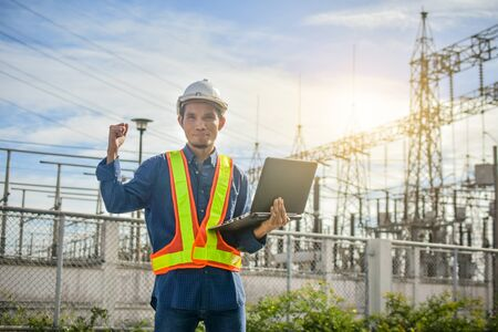 Engineer holding Computer notebook or laptop and a power plant with the Electricity Authority Industrial technology concept