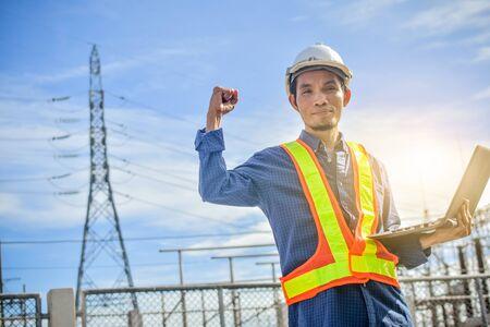 Ingenieur, der ein Computer-Notebook oder einen Laptop und ein Kraftwerk mit dem Industrietechnologiekonzept der Elektrizitätsbehörde hält Standard-Bild